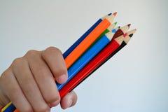 Карандаши цвета владением маленького ребенка Стоковая Фотография RF