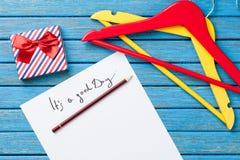 Карандаш и бумага с надписью около вешалок и подарочной коробки Стоковые Фото