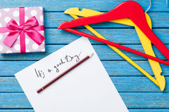 Карандаш и бумага с надписью около вешалок и подарочной коробки Стоковые Изображения RF