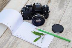Карандаш и лист камеры тетради на винтажной таблице Стоковые Изображения RF