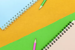 карандаш и тетрадь на красочной бумажной предпосылке Стоковое Изображение RF