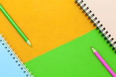 карандаш и тетрадь на красочной бумажной предпосылке Стоковые Изображения