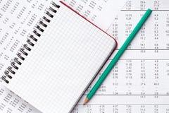 Карандаш и тетрадь на финансовой диаграмме Стоковое фото RF