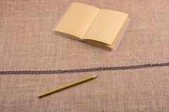 Карандаш и тетрадь с цепью в середине Стоковое Фото