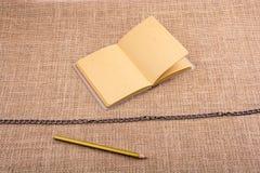 Карандаш и тетрадь с цепью в середине Стоковое фото RF