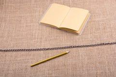 Карандаш и тетрадь с цепью в середине Стоковая Фотография