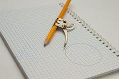 Карандаш, компас, тетрадь на таблице Канцелярские принадлежности для schoolbo Стоковые Изображения