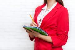 Карандаш тетради владением коммерсантки пишет куртку красного цвета носки Стоковые Фотографии RF