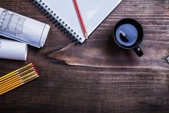 Карандаш тетради с прописями blueprints деревянные метр и чашка  Стоковые Фотографии RF