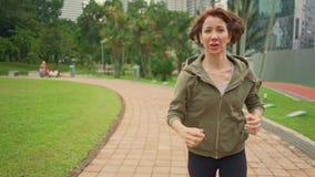 карданный подвес снял отслеживать молодую женщину привлекательных и пригонки в hoodie бежать на зеленом парке города в jogging ут акции видеоматериалы
