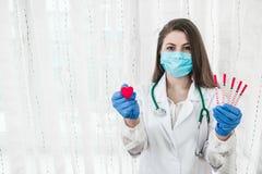 Кардиолог доктора с красными сердцем и шприцами стоковые изображения rf