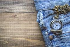 Карманный вахта в карманном старом Джине на деревянной предпосылке Стоковое Фото