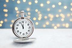 Карманный вахта на таблице против запачканных светов christmas countdown стоковая фотография