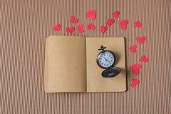 Карманный вахта на тетради с красными бумажными сердцами вокруг стоковые фотографии rf