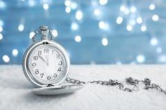Карманный вахта с снегом на таблице против запачканных светов christmas countdown стоковые изображения rf