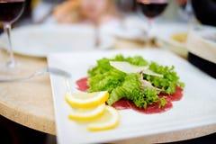 Карпаччо из говядины с кусками салата, сыра пармезан и лимона служило на блюде в ресторане стоковые фотографии rf
