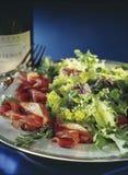 Карпаччо из говядины с салатом и вилкой стоковые изображения