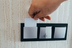 Карта вставки руки крупного плана ключевая к раскрывая свету электронному в гостиничном номере Карта гостиничного номера ключевая стоковое фото rf