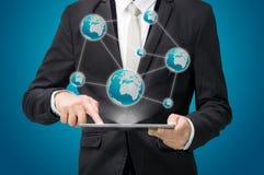 Карта глобуса владением руки позиции бизнесмена стоящая на таблетке Стоковые Фотографии RF