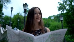 Карта девушки туристская смотря, успешно находит путь к исторической привлекательности стоковое изображение