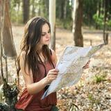 Карта девушки outdoors путешествует самостоятельно в лесе Стоковое Изображение