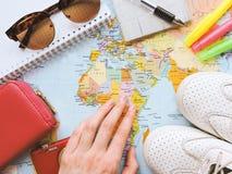 Карта мира в руках человека смотря карты Стоковая Фотография
