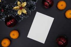 Карта оформления и белой бумаги рождества на черной предпосылке Вертикальная пустая карта Взгляд сверху состава рождества стоковые изображения rf