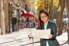 Карта чтения девушки на улицах Парижа с чемоданом Стоковые Фотографии RF