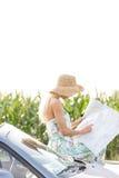 Карта чтения женщины пока полагающся на автомобиле с откидным верхом против ясного неба Стоковая Фотография RF