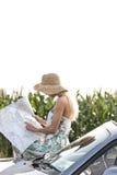 Карта чтения женщины пока полагающся на автомобиле с откидным верхом Стоковая Фотография