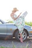 Карта чтения женщины пока сидящ на автомобиле с откидным верхом Стоковые Изображения RF