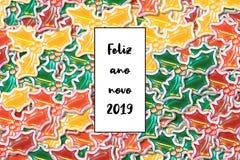 Карта novo 2019 ano Feliz С Новым Годом! на португальском с покрашенными листьями падуба как предпосылка стоковое изображение