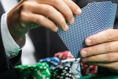Картежник играя карточки покера с обломоками покера на таблице покера Стоковая Фотография