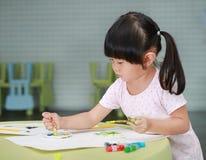 Картина девушки ребенка с цветами paintbrush и воды Стоковая Фотография RF