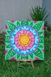 Картина, крася положение мандалы на мольберте, outdoors в траве, яркие цвета стоковые изображения