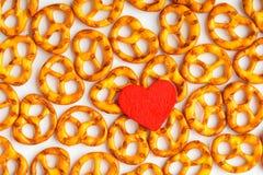Картина кренделей предпосылки дня валентинки и красное сердце. Стоковое фото RF