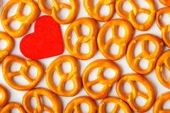 Картина кренделей предпосылки дня валентинки и красное сердце. Стоковые Изображения RF