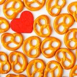 Картина кренделей предпосылки дня валентинки и красное сердце. Стоковые Изображения