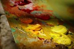 Картина маслом цвета смешивания щетки художника на палитре Стоковая Фотография