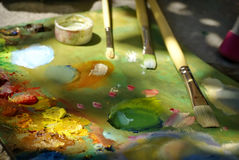 Картина маслом цвета смешивания щетки художника на палитре Стоковые Фотографии RF