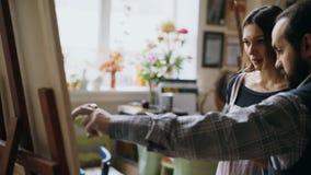 Картина молодой женщины умелого человека художника уча на мольберте на студии художественного училища - людях творческих способно стоковые фото