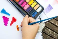 Картина ребенка с краской акварели на книге белой бумаги Стоковая Фотография