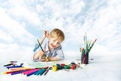 Картина ребенка с щеткой цвета, чертегными инструментами Стоковое Фото
