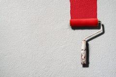 Картина ролика краски с красной краской на белой стене Стоковое Фото