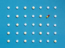 Картина с белыми таблетками и одно покрасили пилюльку на голубой предпосылке Концепция фармации здравоохранения медицины Стоковые Изображения