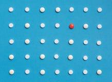 Картина с белыми таблетками и одно покрасили таблетку на голубой предпосылке Концепция фармации здравоохранения медицины Стоковое Фото