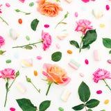 Картина с розами цветет, бутоны, листья и зефир с конфетой на белой предпосылке Плоское положение, взгляд сверху Предпосылка лета Стоковое Изображение
