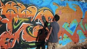 Картина художника граффити на стене улицы Красивый человек при бутылка аэрозольного баллона распыляя с красочной краской, городск сток-видео
