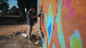 Картина художника граффити на стене улицы Красивый человек при бутылка аэрозольного баллона распыляя с красочной краской, городск акции видеоматериалы