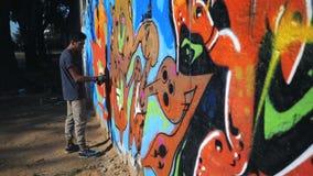 Картина художника граффити на стене улицы Красивый человек при бутылка аэрозольного баллона распыляя с красочной краской, городск видеоматериал